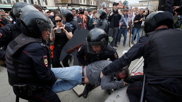 Nikolai Tuzhilin, husband of activist Yulia Galyamina, is detained by riot police during an anti-corruption protest organised by opposition leader Alexei Navalny, on Tverskaya Street in central Moscow, Russia June 12, 2017. REUTERS/Maxim Shemetov - RTS16R35