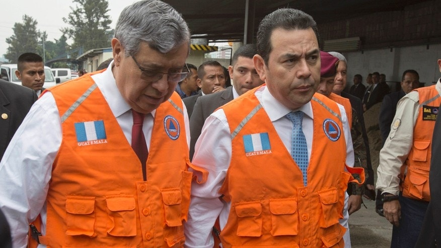 Guatemala's President Jimmy Morales, right, accompanied by his Vice-President Jafeth Cabrera talk as they arrive to National Emergency Coordination Agency's headquarters in Guatemala City, Wednesday, June 14, 2017. Morales says two people died in a magnitude 6.9 earthquake in western Guatemala near the border with Mexico on Wednesday. (AP Photo/Moises Castillo)