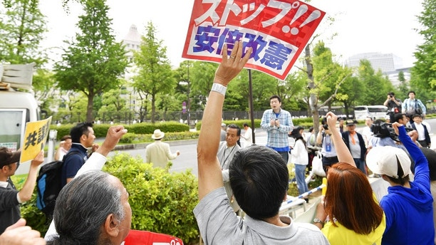 People protesting against Prime Minister Shinzo Abe's policies raise clenched fists outside parliament, background, in Tokyo Abe's ruling coalition pushed a conspiracy bill that makes it a crime to plan a crime