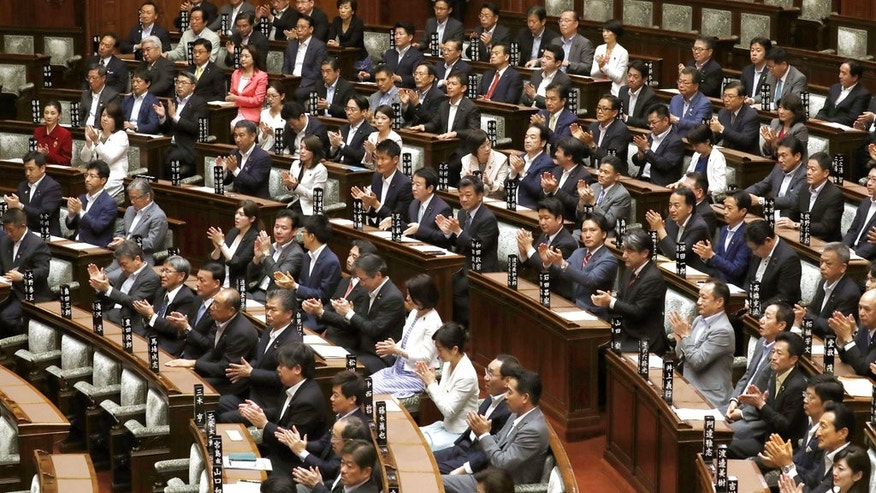 Upper house members of the ruling coalition clap their hands after parliament approved a contentious bill that makes it a crime to plan a crime, in Tokyo Thursday, June 15, 2017. The ruling coalition pushed the conspiracy legislation through the upper house, bypassing committee approval that normally precedes a vote by the full house. (Kyodo News via AP)