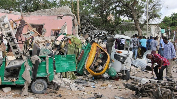 Somalis walk near destroyed vehicles at the scene of a car bomb blast and gun battle targeting a restaurant in Mogadishu, Somalia Thursday, June 15, 2017. Somali survivors early Thursday described harrowing scenes of the night-long siege of a popular Mogadishu restaurant by al-Shabab Islamic extremists that was ended by security forces. (AP Photo/Farah Abdi Warsameh)