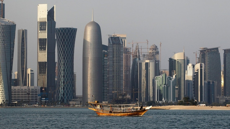 In this Thursday Jan. 6, 2011 file photo, a traditional dhow floats in the Corniche Bay of Doha, Qatar, with tall buildings of the financial district in the background.