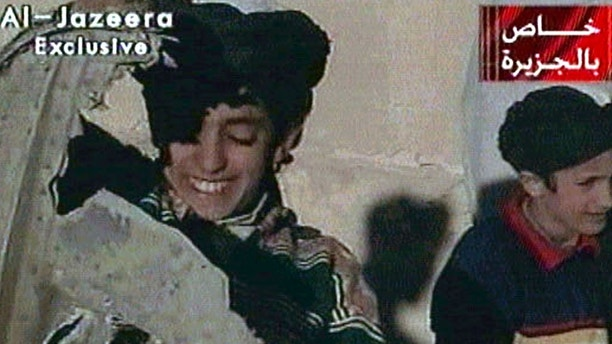 Picture taken from undated Al Jazeera television footage purportedly shows Hamza bin Osama bin Laden (L), one of the sons of Saudi-born dissident Osama bin Laden, displaying what the Taliban say is wreckage from a U.S. helicopter near Ghazni. Child at right is unidentified. [ U.S. B-52  bombers continued to pound the front line of Taliban forces north of the Afghan capital November 7, 2001.    ]  POOR QUALITY VIDEO DOCUMENT (CREDIT REUTERS/Al-Jazeera TV) - RTXKW1N