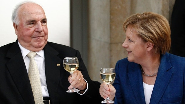 Former German Chancellor Helmut Kohl (L) toasts with glasses of white wine with German Chancellor Angela Merkel after a ceremony of the Christian Democratic Union (CDU) party to mark the upcoming 20-year anniversary of the German unification in Berlin October 1, 2010.        REUTERS/Fabrizio Bensch (GERMANY - Tags: POLITICS) - RTXSWNT