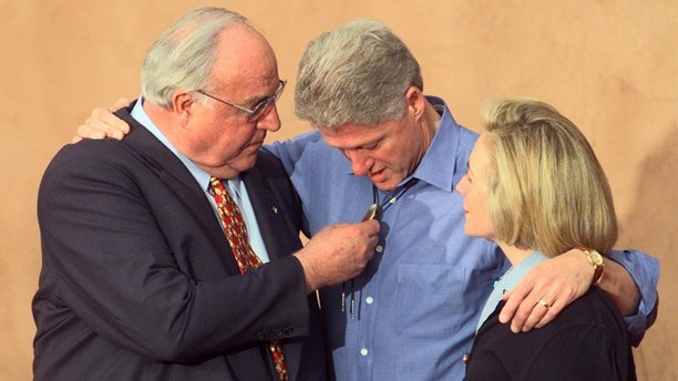 Germany's Chancellor Helmut Kohl (L) admires the western style bolo tie worn by U.S. President Bill Clinton as First Lady Hillary Clinton watches at The Fort Restaurant at the Dever Summit of the Eight June 21. [Clinton had asked the leaders to wear cowboy boots and casual wear to the dinner, however, Kohl refused and kept to the standard coat and tie].  