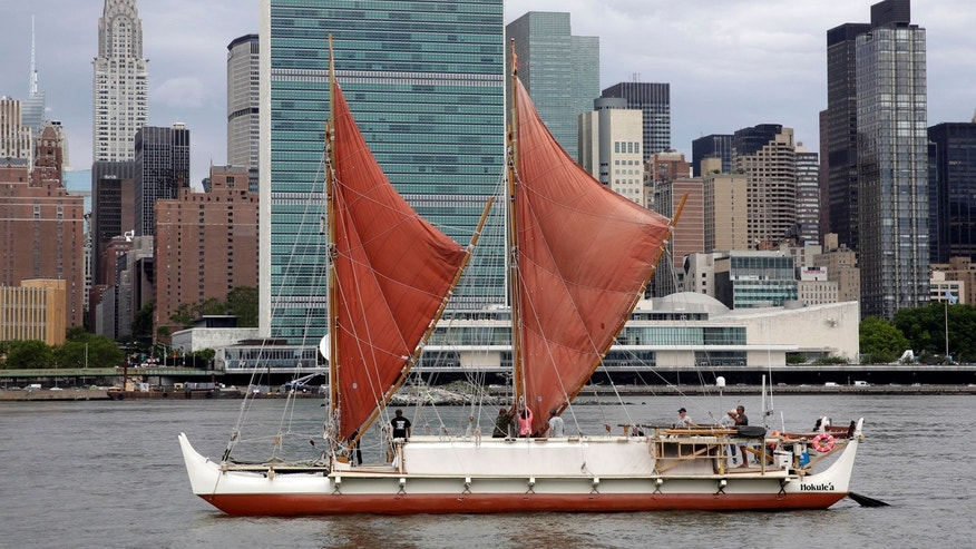 In this June 8, 2016, file photo, the traditional Polynesian voyaging canoe Hokulea, on an around-the-world journey, sails by the United Nations on New York's East River, during the World Oceans Day observance.