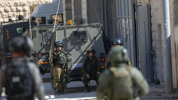 Israeli security forces raid the West Bank village of Deir Abu Mash'al near Ramallah, Saturday, June 17, 2017. Israel security forces raided the village a day after an attack in Jerusalem killed a police officer. The three Palestinian attackers were from the village. (AP Photo/Nasser Shiyoukhi).