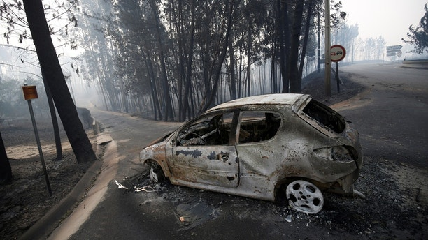 A burned car is seen in the aftermath of a forest fire near Pedrogao Grande, in central Portugal, June 18, 2017.  REUTERS/Rafael Marchante - RTS17IZ2