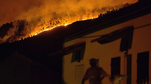 A man on the balcony of a house looks up at a forest fire raging on a hillside above the village of Avelar, central Portugal, before sunrise Sunday, June 18, 2017. A number of people have been killed in forest fires in central Portugal, many of them trapped in their cars as flames swept over a road Saturday evening. (AP Photo/Armando Franca)