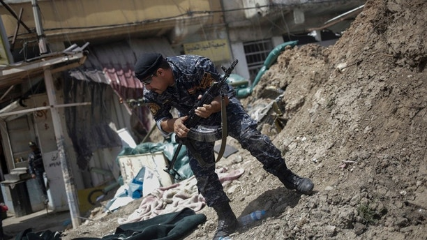 FILE - In this April 29, 2017 file photo, an Iraqi Federal Policeman runs away after he fired shots at an Islamic State group position on the western side of Mosul, Iraq. Iraqi security officials said Wednesday, June 14, 2017 that more than 100 Islamic State militants launched a counterattack in Mosul, killing several Federal Police and civilians in clashes that were still underway. (AP Photo/Bram Janssen, File)