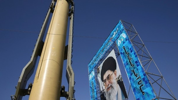FILE - In this Sunday, Sept. 25, 2016, file photo a Ghadr-F missile is displayed next to a portrait of Iranian Supreme Leader Ayatollah Ali Khamenei at a Revolutionary Guard hardware exhibition marking the 36th anniversary of outset of Iran-Iraq war, at Baharestan Sq. in downtown Tehran, Iran. Iran's Revolutionary Guard is warning Islamic State militants that missile attacks launched into eastern Syria the previous day can be repeated if the extremists take action against Iran's security. (AP Photo/Vahid Salemi, File)