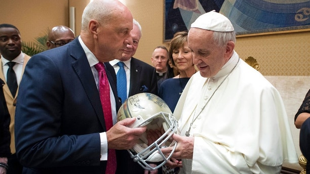 Pope Francis is presented with a Pro Football Hall of Fame helmet by an unidentified member of an NFL Hall of Fame delegation during a private audience at the Vatican, Wednesday, June 21, 2017. (L'Osservatore Romano/Pool Photo via AP)