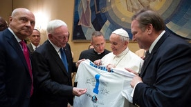 Pope Francis is presented with a Pro Football Hall of Fame jersey bearing his name by Dallas Cowboys owner Jerry Jones, second from left, during a private audience with an NFL Hall of Fame delegation at the Vatican, Wednesday, June 21, 2017. (L'Osservatore Romano/Pool Photo via AP)