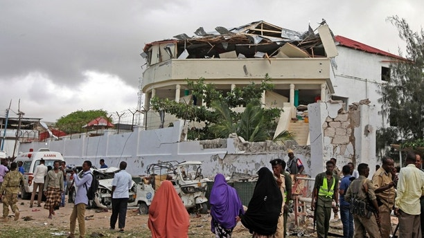 Somalis gather outside a destroyed building near a restaurant that was the scene of a car bomb blast and gun battle in Mogadishu, Somalia Thursday, June 15, 2017. Somali survivors early Thursday described harrowing scenes of the night-long siege of a popular Mogadishu restaurant by al-Shabab Islamic extremists that was ended by security forces. (AP Photo/Farah Abdi Warsameh)