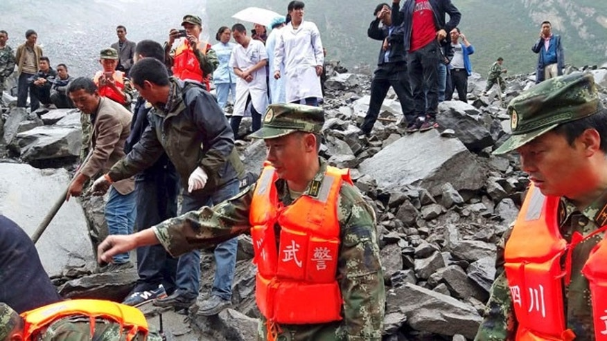 Emergency personnel and local people work at the site of a landslide in Xinmo village Saturday.