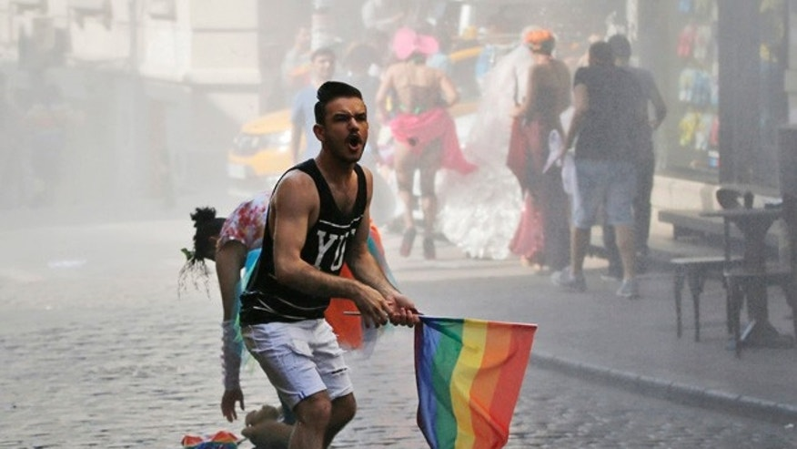 FILE - In this Sunday, June 28, 2015 file photo, a participant of the Pride Week march in Istanbul, reacts as others flee after Turkish police use a water canon to disperse them. For several years, Pride Week in Istanbul attracted tens of thousands of participants, making it one of largest gatherings celebrating gay, lesbian and transgender rights and diversity in the Muslim world. That changed suddenly in 2015, when authorities, citing security concerns, banned gay and trans-gender pride events chasing away shocked participants trying to converge on central Taksim Square with tear gas and water cannons. (AP Photo/Emrah Gurel, File)