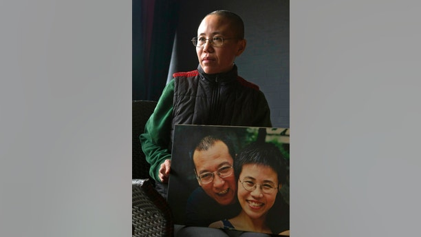 FILE - In this Dec. 6, 2012 file photo, Liu Xia, wife of 2010 Nobel Peace Prize winner Liu Xiaobo, poses with a photo of her and her husband during an interview at her home in Beijing. Jailed Chinese Nobel peace laureate and dissident Liu has been released on medical parole after being diagnosed with late-stage liver cancer, his lawyer said Monday, June 26, 2017. (AP Photo/Ng Han Guan, File)