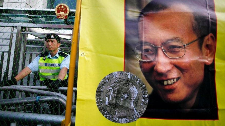 A police officer stands guard beside a picture of jailed Chinese dissident Liu Xiaobo, in December 2010.