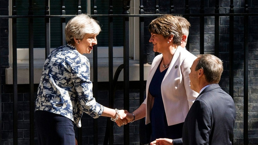 Britain's Prime Minister Theresa May welcomes Democratic Unionist Party (DUP) leader Arlene Foster, center, and DUP deputy leader Nigel Dodds outside 10 Downing Street in London, Monday June 26, 2017. The leader of a Northern Ireland-based party is in London to finalize an agreement with Prime Minister Theresa May's Conservative-led government. (Dominic Lipinski/PA via AP)