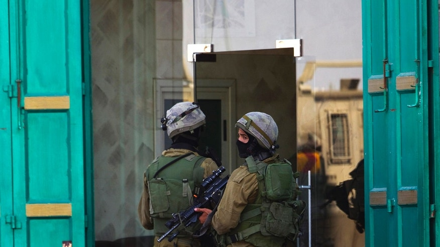 Israeli soldiers enter a shop during an operation to locate three missing teenagers, in the West Bank city of Hebron June 18, 2014. Israel re-arrested 51 Palestinians freed in a 2011 prisoner swap deal in the sixth day of a hunt for the three missing teenagers believed abducted in the occupied West Bank.