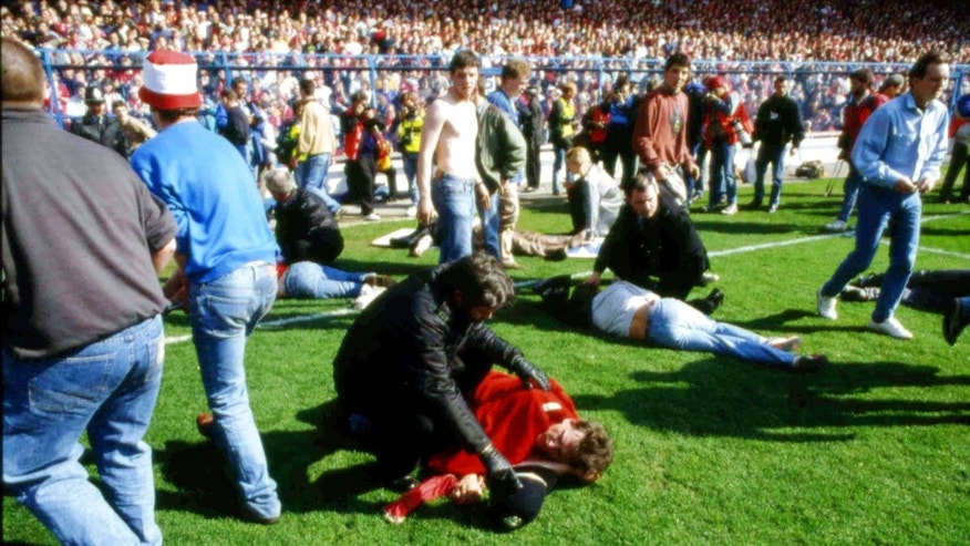 FILE - In this April 15, 1989 file photo, police, stewards and supporters tend and care for wounded supporters on the pitch at Hillsborough Stadium, in Sheffield, England. British prosecutors on Wednesday June 28, 2017, are set to announce whether they plan to lay charges in the deaths of 96 people in the Hillsborough stadium crush _ one of Britain's worst-ever sporting disasters. (AP Photo, File)