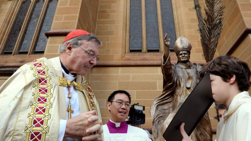 Cardinal George Pell, left, has been charged with historical sexual assault offenses. (AP Photo/Rob Griffith, File)