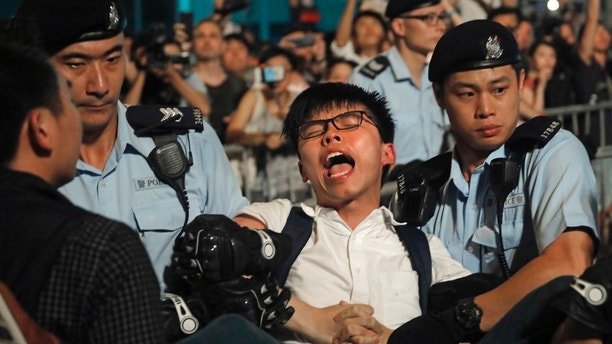 Pro-democracy activist Joshua Wong is detained by police officers after he climb up to a giant flower statue bequeathed by Beijing in 1997 in Golden Bauhinia Square of Hong Kong Wednesday, June 28, 2017.  Hong Kong is planning a big party as it marks 20-years under Chinese rule, ceded from Britain. (AP Photo/Vincent Yu)