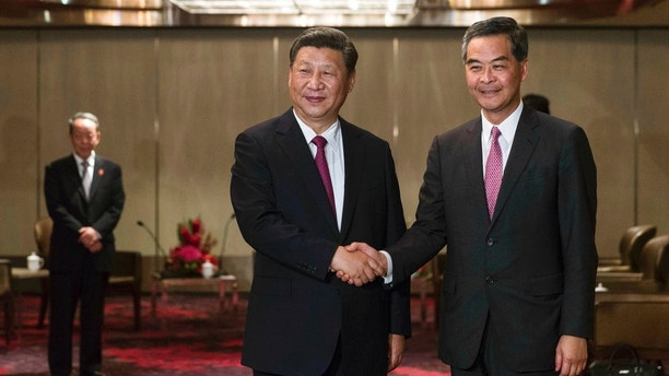 China's President Xi Jinping, left, shakes hands with Hong Kong's outgoing chief executive Leung Chun-ying during a meeting at a hotel in Hong Kong Thursday, June 29, 2017.  Xi was greeted by supporters waving red Hong Kong and Chinese flags as he arrived Thursday to mark two decades since China took control of the former British colony and to inaugurate new chief executive Carrie Lam on July 1. (Dale de la Rey/Pool Photo via AP)