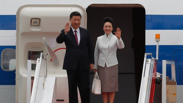 Chinese President Xi Jinping and his wife Peng Liyuan waves after arrived at Hong Kong's airport, Thursday, June 29, 2017. Hong Kong is planning a big party as it marks 20 years under Chinese rule. But many people in the former British colony are not in the mood to celebrate. Fireworks, a gala variety show and Chinese military displays are among the official events planned to coincide with a visit by Chinese President Xi Jinping starting Thursday for the occasion. (AP Photo/Kin Cheung)