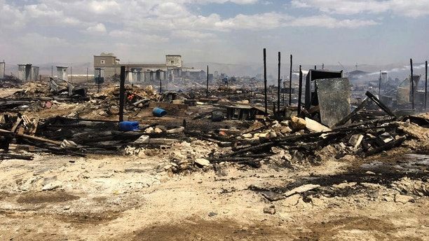 This photo provided by the Qab Elias Emergency Services, shows the charred remains of dozens of tents in a Syrian refugee camp in Qab Elias, a village in the Bekaa Valley, Lebanon, Sunday, July 2, 2017. Lebanon's state news agency and the Red Cross say a major fire has broken out in a Syrian refugee settlement, killing at least one person and sending large plumes of black smoke into the sky. (Qab Elias Emergency Services/Ahmed Salloum via AP)