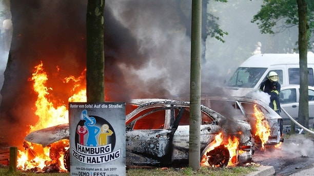 Firefighters work at the scene where a number of cars burnt down during the G20 summit in Hamburg, Germany, July 7, 2017. REUTERS/Hannibal Hanschke - RTX3AEVQ