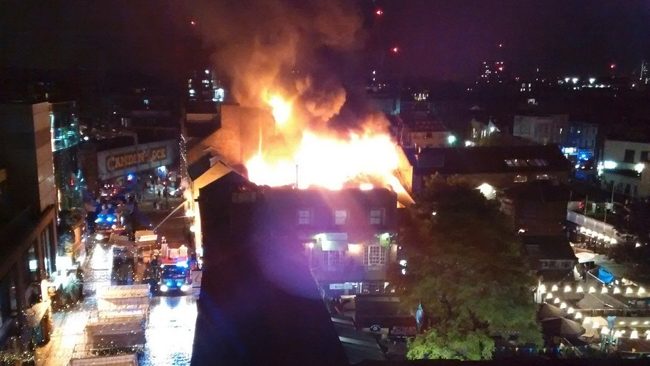 Flames and smoke rise from a fire affecting a small area of Camden Market in London early Monday.