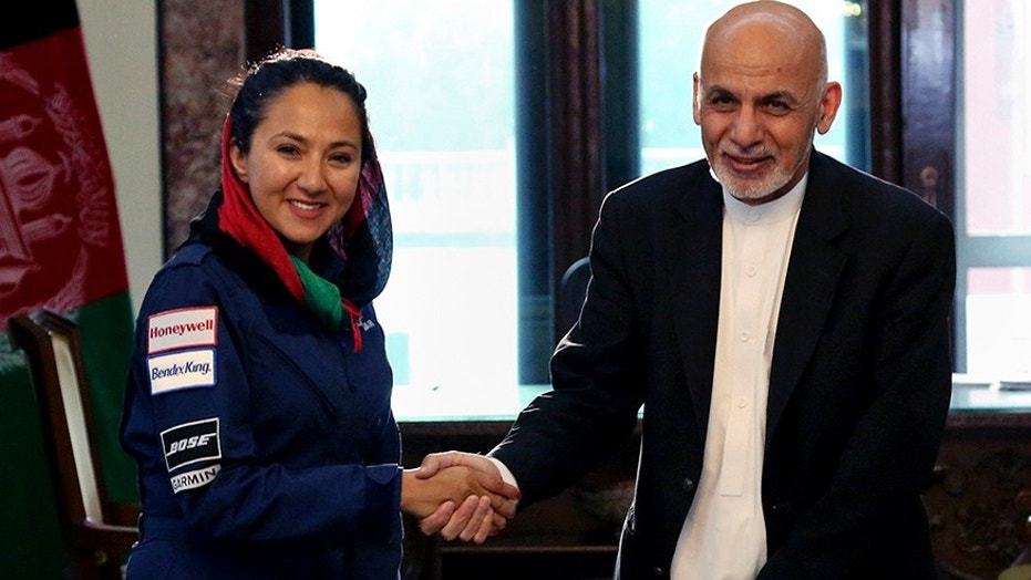 In this Monday, July 10, 2017 photo, Afghan President Ashraf Ghani shakes hands with Afghan-American female pilot Shaesta Waiz at the Presidential Palace in Kabul, Afghanistan. Waiz, who is on a solo flight around the world to inspire young women, has taken a detour to visit Afghanistan. Waiz left her single-engine plane in Dubai, the United Arab Emirates, to take a commercial flight to Kabul where she landed on Monday night. Waiz began her journey in May and has since stopped in 11 countries, with eight more to go. (Afghan Presidential Palace via AP)