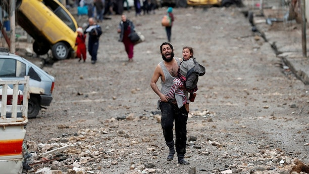 """A man cries as he carries his daughter while walking from an Islamic State-controlled part of Mosul towards Iraqi special forces soldiers during a battle in Mosul, Iraq March 4, 2017. Reuters Photographer Goran Tomasevic: """"Both screaming in terror, a father and the young daughter he cradled in his arm fled through the rubble-strewn streets of Wadi Hajar, transformed in a flash into a battleground between Islamic State fighters and Iraqi special forces. They and their neighbours - some wearing rubber sandals, some barefoot -  were running from an IS counter-attack in this part of Mosul, dodging gunfire as the militants closed in. When they reached the special forces lines, males were ordered to lift their shirts to prove they weren't suicide bombers. Some had to take off their clothes or show their belts, though not those carrying children. The father was so beside himself, so panicked. It was obvious because he had a short shirt on and was carrying a child that he wasn't Islamic State. I believe they will both be taken to a refugee camp."""" REUTERS/Goran Tomasevic  SEARCH """"TOMASEVIC FATHER"""" FOR THIS STORY. SEARCH """"WIDER IMAGE"""" FOR ALL STORIES. TPX IMAGES OF THE DAY - RTS11P35"""