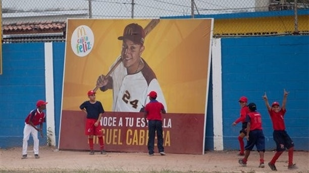 "Two boys stand in front of a fast food advertisement featuring hometown athlete, Detroit Tiger's Miguel Cabrera, during a baseball practice in Maracay, Venezuela, Friday, March 28, 2014. Cabrera's uncle seems unfazed by the news that the Detroit Tigers slugger has netted the richest contract in history of any U.S. sport. Like the rest of the neighborhood, he thinks ""Miguelito,"" as many in his hometown still call him, was destined for greatness. (AP Photo/Alejandro Cegarra)"