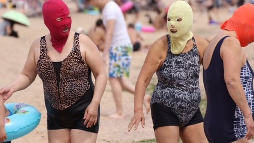 Women wear 'facekinis' on the beach in Qingdao, China this week