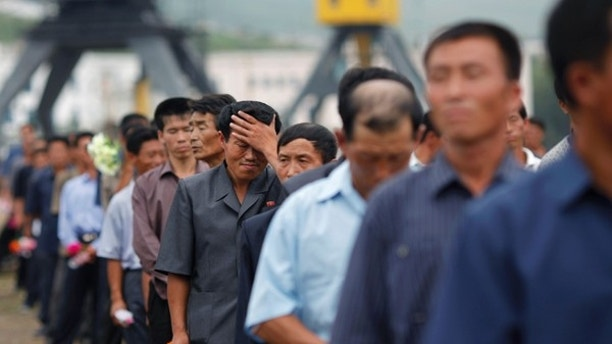 Local residents attend the departure ceremony of the Mangyongbyong cruise ship in the port area of North Korean Special Economic Zone of Rason City, northeast of Pyongyang August 30, 2011. North Korea launched itself into the glitzy world of cruise tourism when about 130 passengers set sail from the rundown port of Rajin, near the China-Russia border, for the scenic Mount Kumgang resort near the South Korean border. Isolated North Korea's state tourism bureau has teamed up with a Chinese travel company to run the country's first ever cruise aboard an ageing 9,700 tonne vessel which once plied the waters off the east coast of the divided peninsula shuttling passengers between North Korea and Japan. Picture taken August 30, 2011. REUTERS/Carlos Barria (NORTH KOREA - Tags: POLITICS TRAVEL SOCIETY) - RTR2QSOB