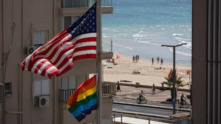 A U.S. flag is raised alongside a pride flag at the U.S. Embassy a day before the Gay Pride Parade in Tel Aviv, Israel, Thursday, June 12, 2014.