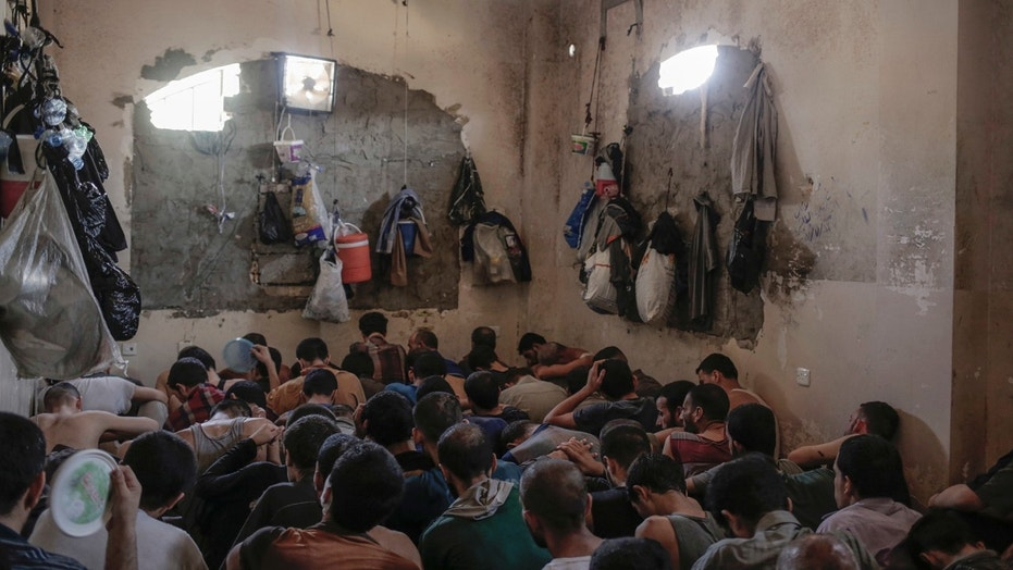 Suspected Islamic State members sit inside a small room in a prison south of Mosul, Tuesday, July 18, 2017.