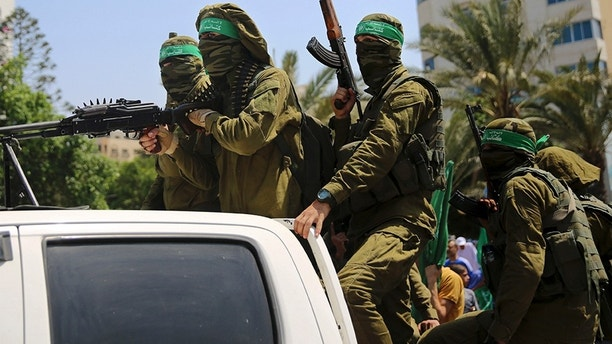 Masked militants from the Izzedine al-Qassam Brigades, a military wing of Hamas, ride vehicles during a protest against metal detectors Israel erected at the Al Aqsa Mosque compound in Jerusalem, at the Palestinian Legislative Council in Gaza City, Friday, July 21, 2017. (AP Photo/Adel Hana)