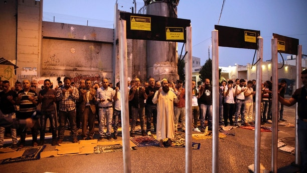 Palestinians pray in front of mock metal detectors during a protest in Bethlehem, Sunday, July 23, 2017. Israel's minister of public security said Sunday that metal detectors set at the entrance to a major Jerusalem shrine that angered Palestinians could be removed if police have another way of ensuring security there. (AP Photo/Mahmoud Illean)