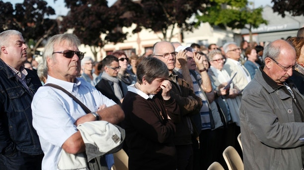 People attend a ceremony marking the first anniversary of the killing of French Catholic priest Jacques Hamel by two jihadists at his church in Saint-Etienne-du-Rouvray, France, Wednesday, July 26, 2017. (AP Photo/Thibault Camus)