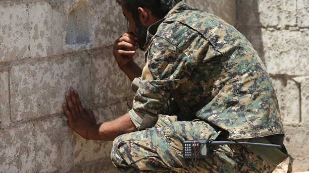 A U.S.-backed Syrian Democratic Forces fighter, looks through a hole on the front line of the industrial district on the eastern side of Raqqa city, northeast Syria, Wednesday, July 26, 2017. (AP Photo/Hussein Malla)
