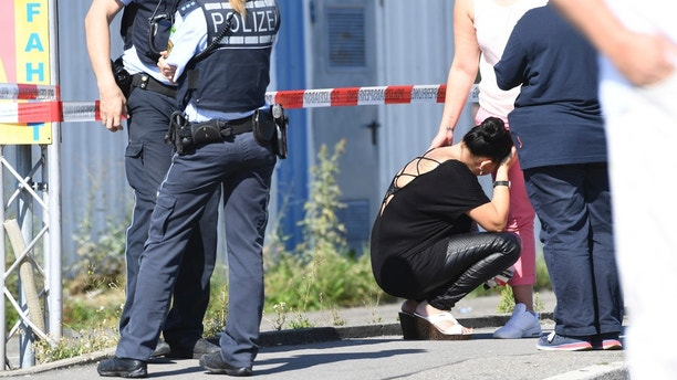 A visitor, center,  waits to be questioned by police near a discotheque in Constance, at Lake Constance, Germany, Sunday, July 30, 2017. Police say a shooting in Germany's Baden-Wurttemberg state has claimed two lives, including that of the gunman. They say the early-morning shooting Sunday at a discotheque in the town of Constance also left three guests seriously wounded. A tweet by Constance police says one person was killed by the shooter when he opened fire, also wounding the other victims. He then fled, was shot by police and died later in hospital.  (Felix Kaestle/dpa via AP)