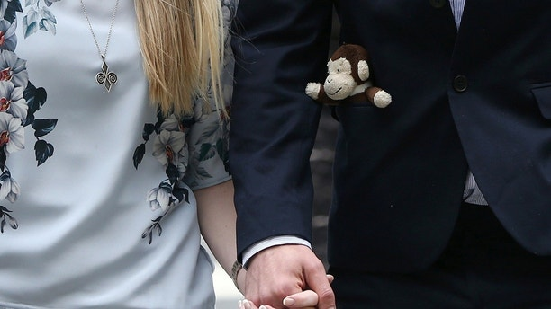 The father of critically ill baby Charlie Gard carries a toy monkey in his pocket as he and Connie Yates, Charlie Gards mother, arrive at the High Court in London, Britain July 14, 2017. REUTERS/Neil Hall - RTX3BGKR