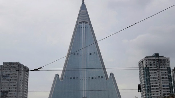 In this Friday, July 28, 2017, photo, people walk past the 105-story pyramid shaped Ryugyong Hotel in Pyongyang, North Korea. Walls set up to keep people out of a construction area around the gargantuan Ryugyong Hotel were pulled down as the North marked the anniversary of the Korean War armistice to reveal two broad new walkways leading to the building and the big red propaganda sign declaring that North Korea is a leading rocket power. (AP Photo/Wong Maye-E)