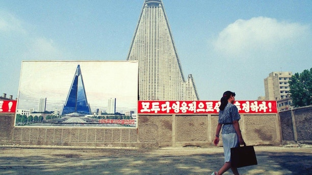 "FILE - In this Aug. 22, 1990, file photo, a woman walks past the site of the Ryugyong Hotel under construction in Pyongyang, North Korea. Sign in red reads ""Let's all together struggle heroically!"" Walls set up to keep people out of a construction area around the gargantuan Ryugyong Hotel were pulled down in July 2017 as the North marked the anniversary of the Korean War armistice to reveal two broad new walkways leading to the building and the big red propaganda sign declaring that North Korea is a leading rocket power. (AP Photo/Vincent Yu, File)"