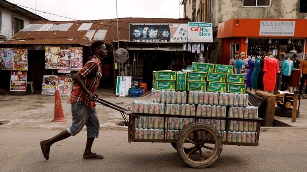 A man pushes a cart containing packets of locally made beer along a road in Agege district in Nigeria's commercial capital Lagos July 26, 2017.REUTERS/Akintunde Akinleye - RTX3D1IH