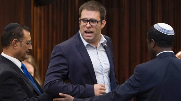 This Wednesday June 17, 2015 file photo shows Oren Hazan, a Likud party parliament member, being escorted out of the parliament hall by ushers. The Israeli lawmaker has been forced to call off a 'non-violent' faceoff with a Jordanian challenger after Prime Minister Benjamin Netanyahu's office ordered him to stand down. (AP Photo/Emil Salman, File) ***ISRAEL OUT***