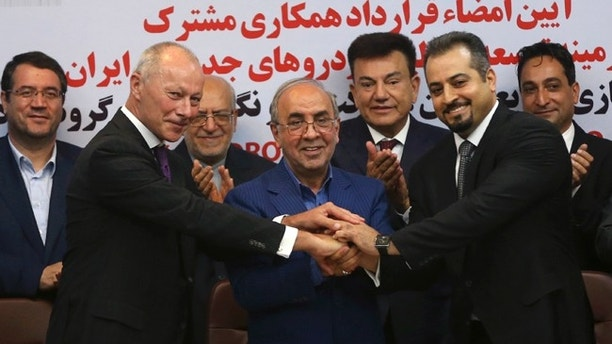Chief Competitive Officer of Groupe Renault Thierry Bolloré, left, Chairman of Industrial Development and Renovation Oraganization of Iran, IDRO, Mansour Moazami, center, and Negin Group CEO Kourosh Morshed Solouk join hands after signing a deal in Tehran, Iran, Monday, Aug. 7, 2017. Iran signed the country's biggest-ever car deal with French multinational automobile manufacturer Groupe Renault on Monday to produce 150,000 cars, beginning in 2018. (AP Photo/Vahid Salemi)